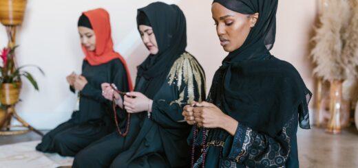 Donne islamiche con velo che pregano in ginocchio